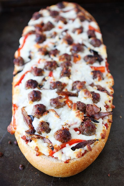 Easy French Bread Pizza with Sausage, Caramelized Onions, and Roasted Red Peppers on twopeasandtheirpod.com