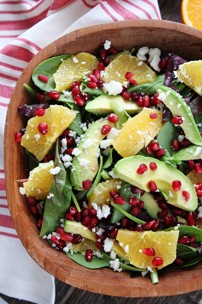 top mixed greens with pomegranate seeds, orange slices, avocado slices ...